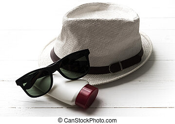 hat sunglasses and body lotion
