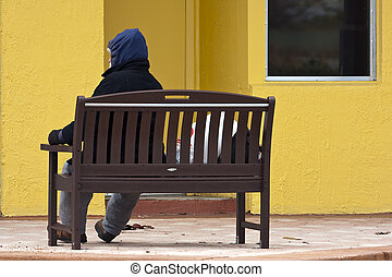 Homeless Man - A homeless man sitting on a bench in front of...