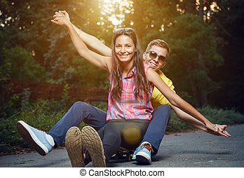 Young couple in love sitting on a skateboard outdoors