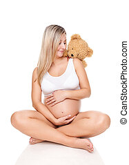 Portrait of a pregnant woman sitting on floor and holding belly