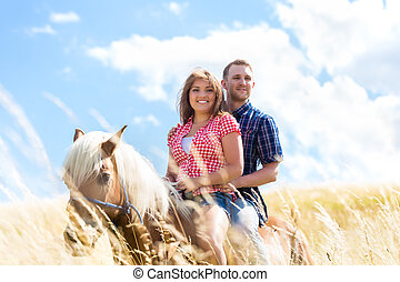Couple riding on horse in summer meadow