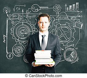 Businessman with books and business strategy scheme concept on the blackboard