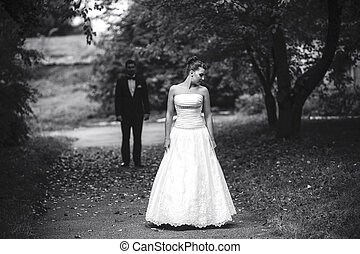 Bride waiting for her bridegroom, who stands behind her in...