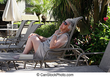 elderly woman relaxing in pool lounge chair