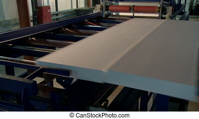 Finished sandwich panels moves along conveyor, close-up