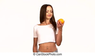 Young, sporty, slim woman with an orange and apple, choice, on white