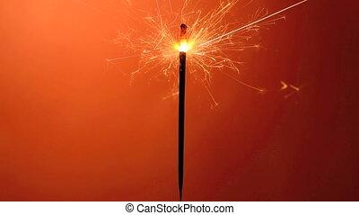 Burning sparkler in front of an orange background