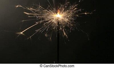 Burning sparkler in front of a black background
