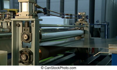 Production material passes from machines reel - View of...