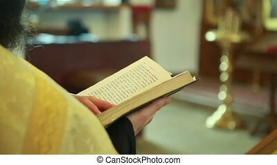 The priest in the Church shatters the page in the Bible