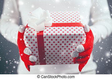 Woman offering Christmas gift in wrapped box, holiday season...