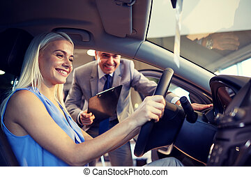 happy woman with car dealer in auto show or salon - auto...