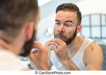 Man plucking his nasal hairs - Handsome bearded young man...