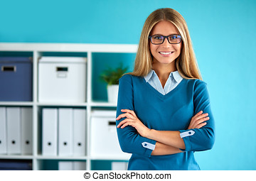 Smiling business woman standing in office with crossed arms