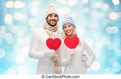 smiling couple in winter clothes with red hearts - love,...