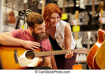 couple of musicians with guitar at music store - music,...