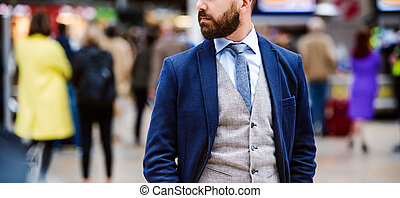 Businessman at the station - Young handsome businessman...