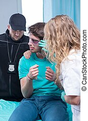 Injured man with policeman and doctor - Picture of injured...