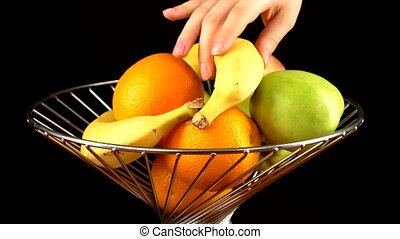 Fruits in vase, taking by two persons, on black - Fruits in...