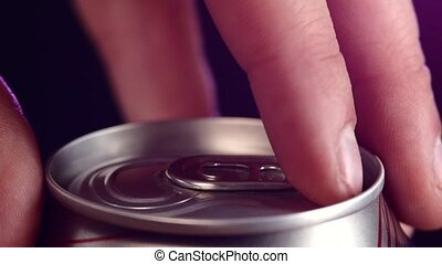 Hand opening can with spray, splash, on black, slow motion -...