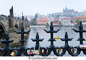 Prague riverbank with locks of love on the fence,