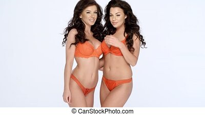 Gorgeous shapely women in orange lingerie - Two happy...