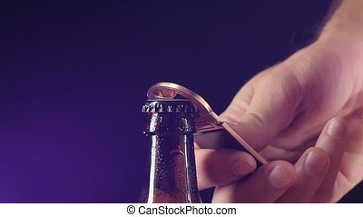 Opening with bottle opener on dark, slow motion - Opening...