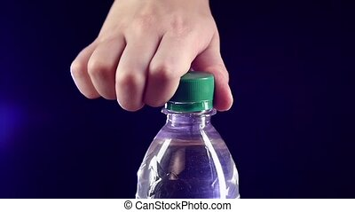 Hands opening a green bottle of fresh water on dark, slow...