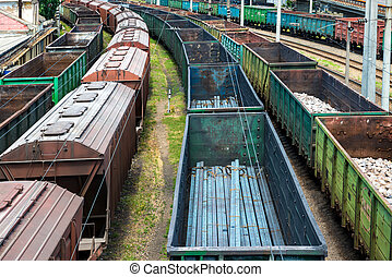 Many trains with cargo wagons on the railroad