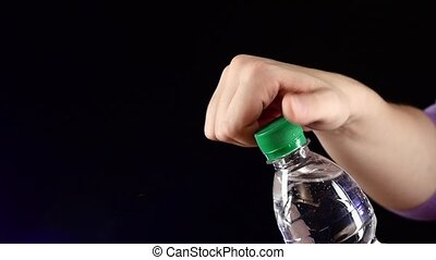 Hands up and opening a green bottle of fresh water on dark,...
