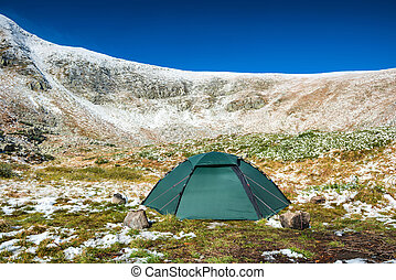 Green tent in snow mountains Beautiful spring landscape