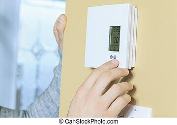 man set the thermostat at house.