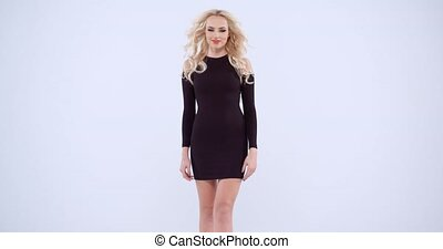 Lovely stylish young blond woman in a chic black miniskirt...
