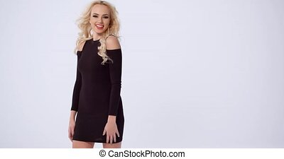 Vivacious trendy young blond woman posing in a stylish black...
