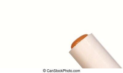 Opening orange lipstick isolated on white, slow motion