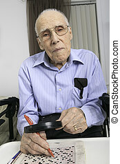 elderly man sitting doing crosswords hobby - A elderly man...