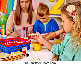 Kids with teacher holding colored paper and glue on table in kindergarten .
