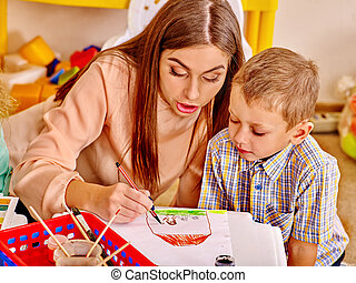 Woman with kids holding colored paper and glue in...