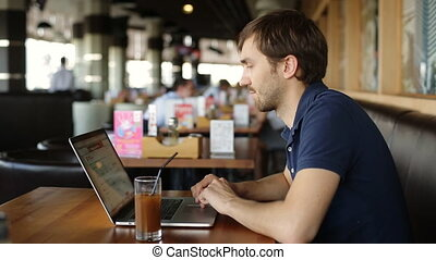 serious man with laptop in cafe and found information