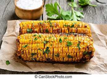 Corn cobs grilled on baking paper, close up view