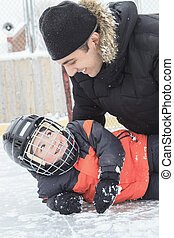 Father son hockey - A father with is son on a hockey goal in...