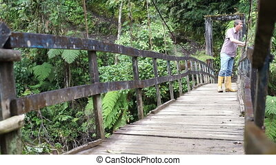 Man Walks on Hanging Bridge Coming - Hiking man in yellow...
