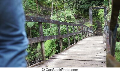 Man Walks on Hanging Bridge Going - Hiking man in yellow...