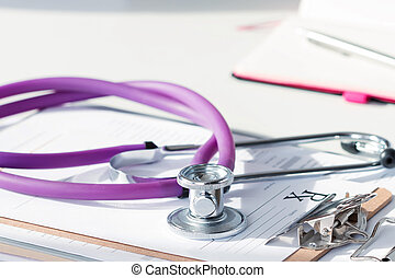 Stethoscope lying on pad with prescription form. Medicine...