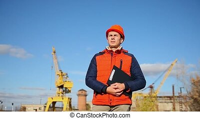 builder man in a helmet shows a finger away orange against...