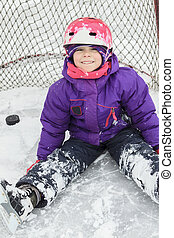 child on the hockey ice with a puck. - A child on the hockey...