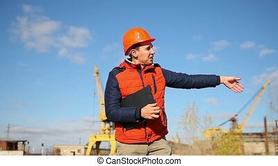 male construction worker in an orange helmet waving calling runs behind the crane and blue sky