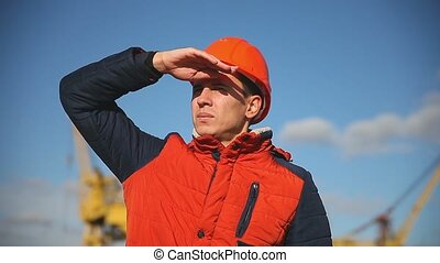 Portrait of a man builder in orange helmet looks into the distance against the blue sky and building