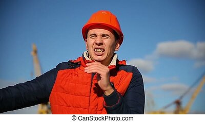 Portrait of a man builder in orange helmet shouts calling waving against a blue sky and construction
