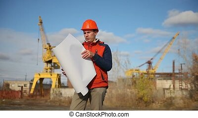 Portrait of man builder in orange helmet looks instruments project against the blue sky and building